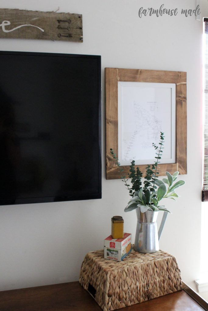 Awful with gallery walls? Me too. Give it up and go simple with this idea to decorate around a giant tv with wood frames and a sign!