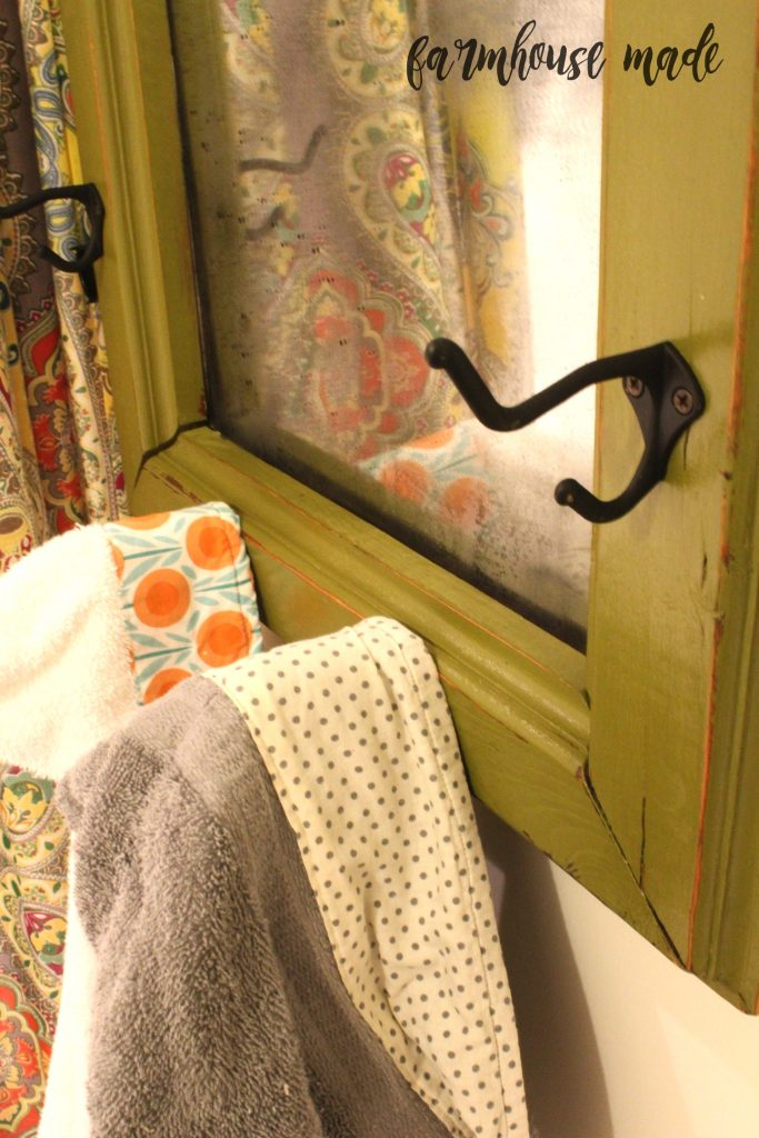 This old mirror transformed to a chippy farmhouse mirror with adorable knobs and hooks was the perfect flip for the kids' bathrooms!