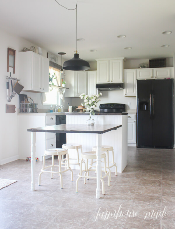 The rustic, handmade kitchen island/table combo pop in the kitchen now these cabinets are painted Alabaster. The darker accents help blend in the black appliances, until we upgrade our counter tops! Get all the best tips and a realistic timeline in this post!