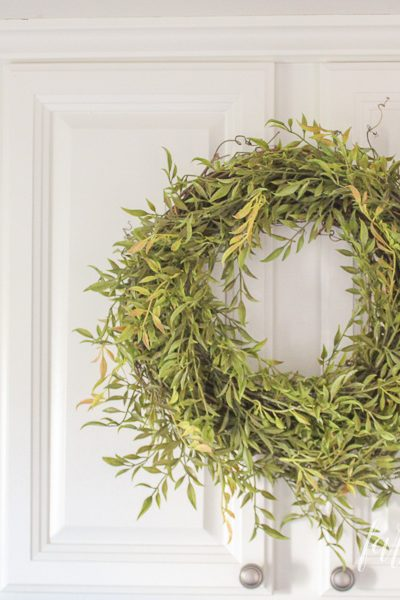 How adorable is this smilax greenery wreath!? Would you believe I made it in 5 minutes for under $15? I did, and you can whip these things up so fast, with barely any supplies. Wreaths look beautiful everywhere, except their price tags. Come learn to make this gorgeous greenery wreath!