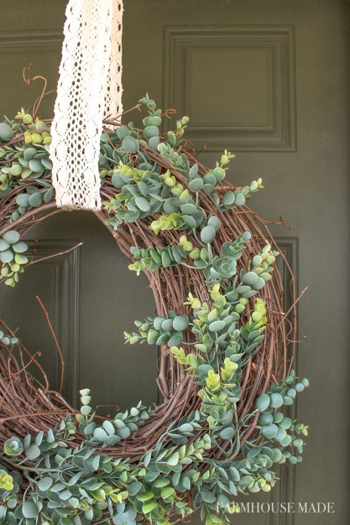 Loving the haphazardness of the eucalyptus garland on the grapevine garland wreath! What an adorable spring wreath - It lays so nicely, and is a fresh and welcoming sight on the olive green door! #wreath #springwreath #diywreath