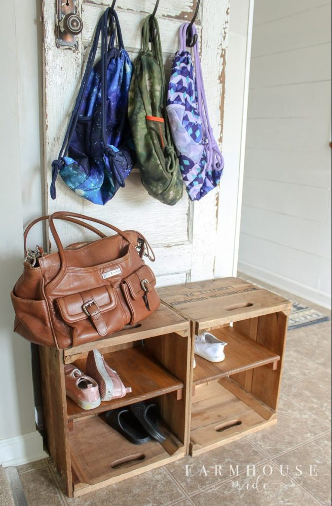 Apple bushel box storage cubbies holding shoes, tote, and backpacks