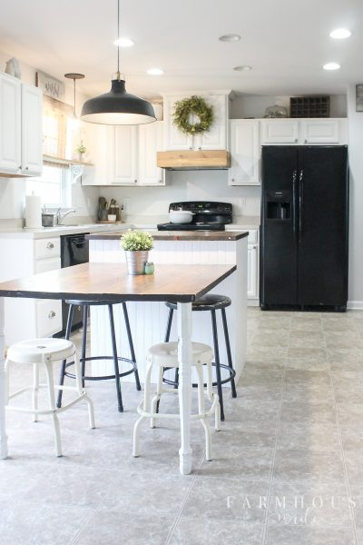 White, bright, farmhouse kitchen with white painted cabinets, island, and barn light