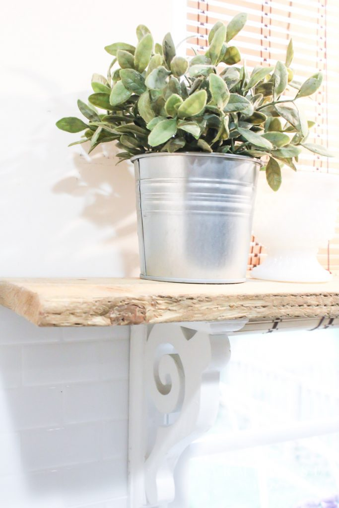 Herb shelf in farmhouse style kitchen with white corbels and light stain