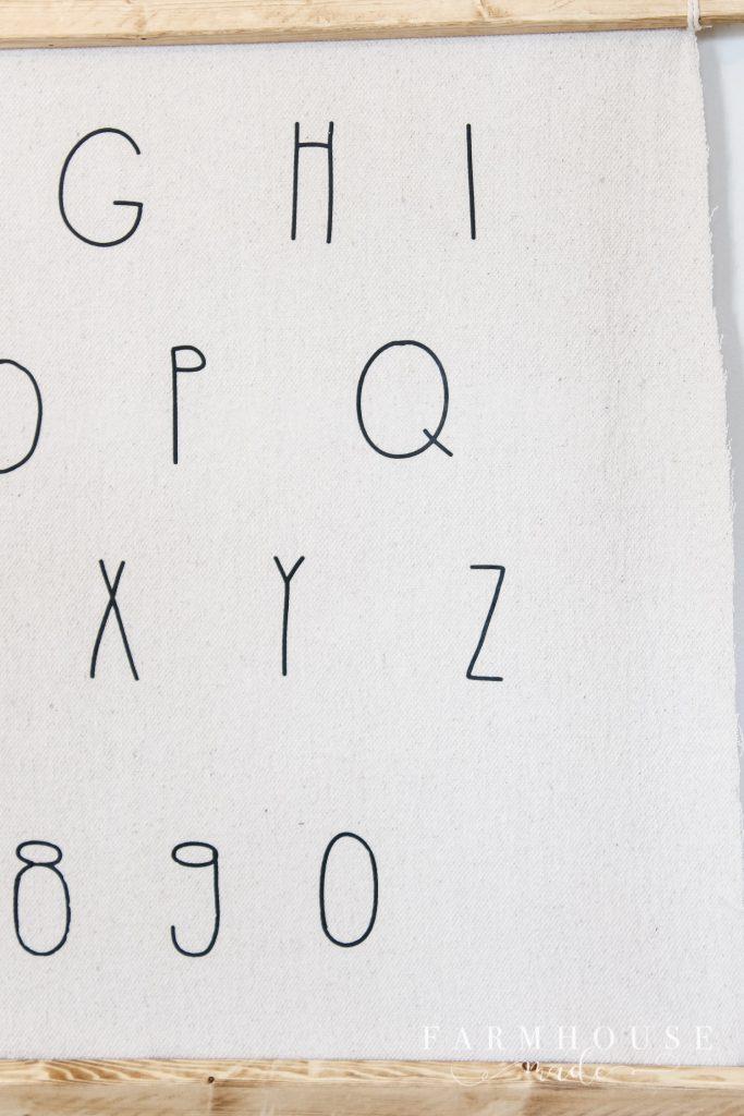 Closeup of iron on vinyl letters on drop cloth diy alphabet wall art