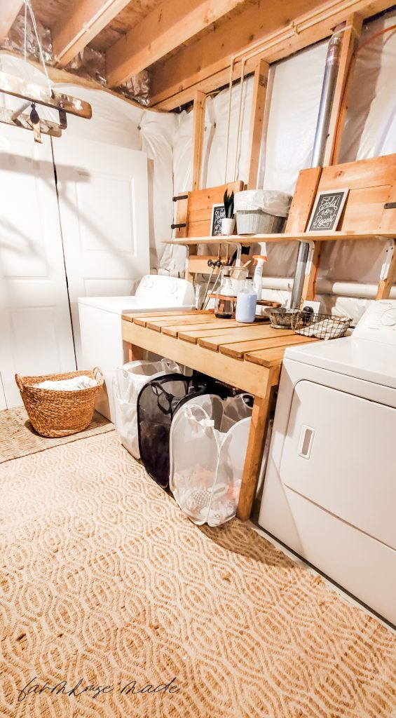 How to Control Laundry Like A Tired Mom - Basement Laundry Room with Folding Table and Baskets for Kids